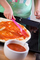 Small child spreading tomato sauce on pizza dough