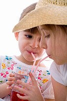Two girls drinking fruit juice out of one glass with straws