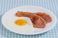 Bacon and egg on a plate, checked tablecloth