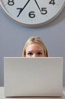 una donna seduta al computer e un grande orologio alle spalle