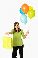Teenage girl holding balloons and shopping bag or gift bag