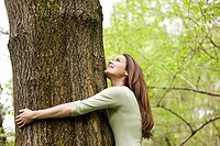 A young woman hugging a tree