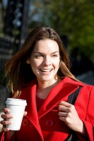 A young woman in a red coat holding a hot drink