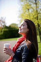 A young woman enjoying the sun, holding a hot drink