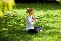 A mid adult woman meditating in the park