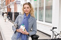 A mid adult woman holding a newspaper and a pint of milk (thumbnail)