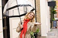 A mid adult woman holding an umbrella, checking for rain