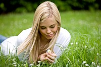 A young woman lying on the grass, looking at a daisy