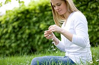 A young woman sitting on the grass, holding a daisy chain