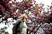 A young woman standing under a tree in springtime