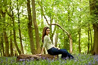 A young woman sitting on a log, resting (thumbnail)