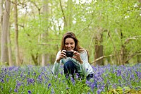 A young woman photographing bluebells, smiling (thumbnail)