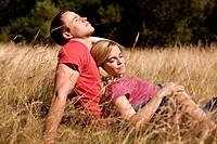 A young couple sitting in the grass together, enjoying the sun