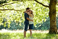 A young couple standing beneath a tree, embracing (thumbnail)