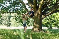 A young woman talking to her boyfriend up a tree (thumbnail)