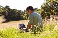 A young man sitting on the grass, using a laptop