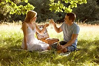 A young couple having a picnic, making a toast