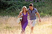A young couple walking through a field arm in arm