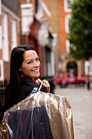 A businesswoman carrying her dry cleaning