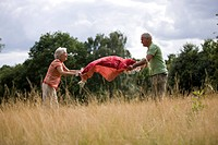 A senior couple laying a picnic blanket on the grass