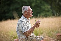 A senior man sitting on the grass, eating