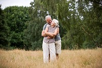 A senior couple standing in a field, embracing