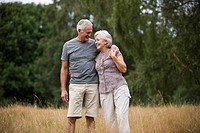 A senior couple standing in a field, embracing (thumbnail)