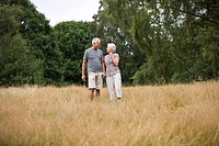 A senior couple standing in a field, holding hands