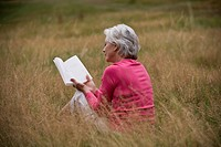 A senior woman sitting on the grass, reading a book, rear view (thumbnail)
