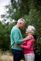 A senior couple looking into each other's eyes, outdoors