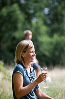 A middle aged woman sitting on the grass, having a glass of wine
