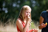 A young girl sitting on the grass, eating an orange