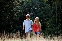 A young boy and girl walking through a field