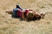 A young couple lying on the grass, embracing