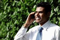Cropped shot of Indian man talking on phone and smiling
