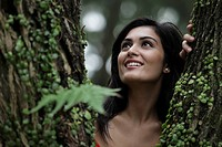 Head shot of young woman looking through a tree and smiling
