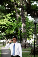 Indian man talking on phone under trees