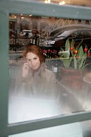 Business woman with mobile phone and laptop in a restaurant