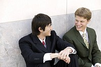 Two young men are greeting each other.