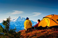 A man and woman sitting by their tent in Peters Hills with Mt. McKinley in the background, Denali State Park, Southcentral Alaska, Fall/n