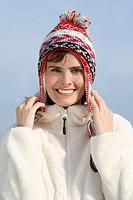 portrait of brunette woman in autumn landscape wearing wooly hat