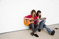 Two girls sitting on floor with guitar (thumbnail)