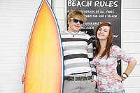 Young couple with surfboard, portrait