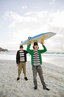Young men carrying surfboard on head