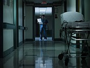 Doctor reading medical chart in hospital corridor