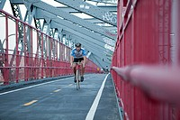 Man cycling over bridge