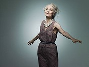 Senior woman with arms out, portrait (thumbnail)