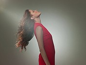 Young woman wearing red dress leaning back, portrait