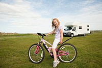 Girl with a bicycle near caravan