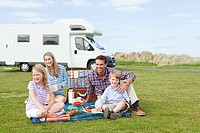 Family having picnic by caravan